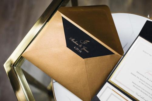 Gold Foil Monogram on black pocket with antique gold envelope