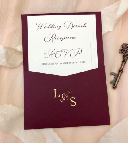Burgundy pocket wedding invitation with gold foil monogram
